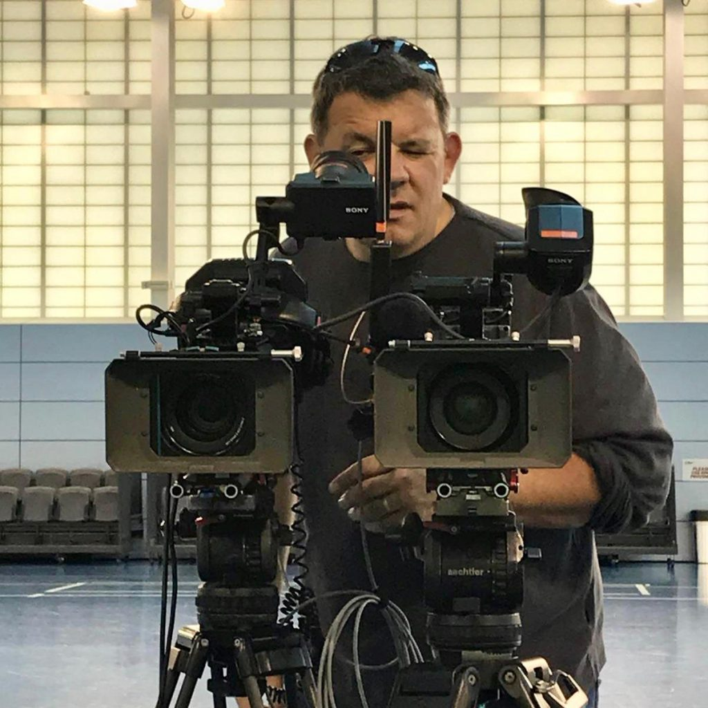 mark standing behind two cameras, looking in the viewfinder
