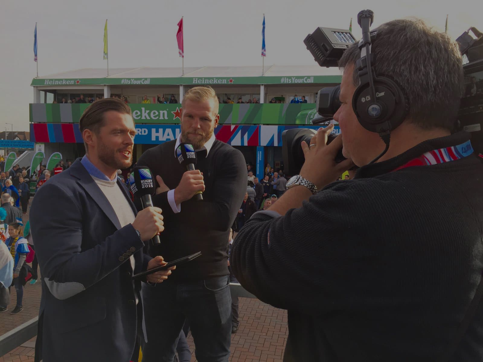 mark behind the camera interviewing two people holding microphones