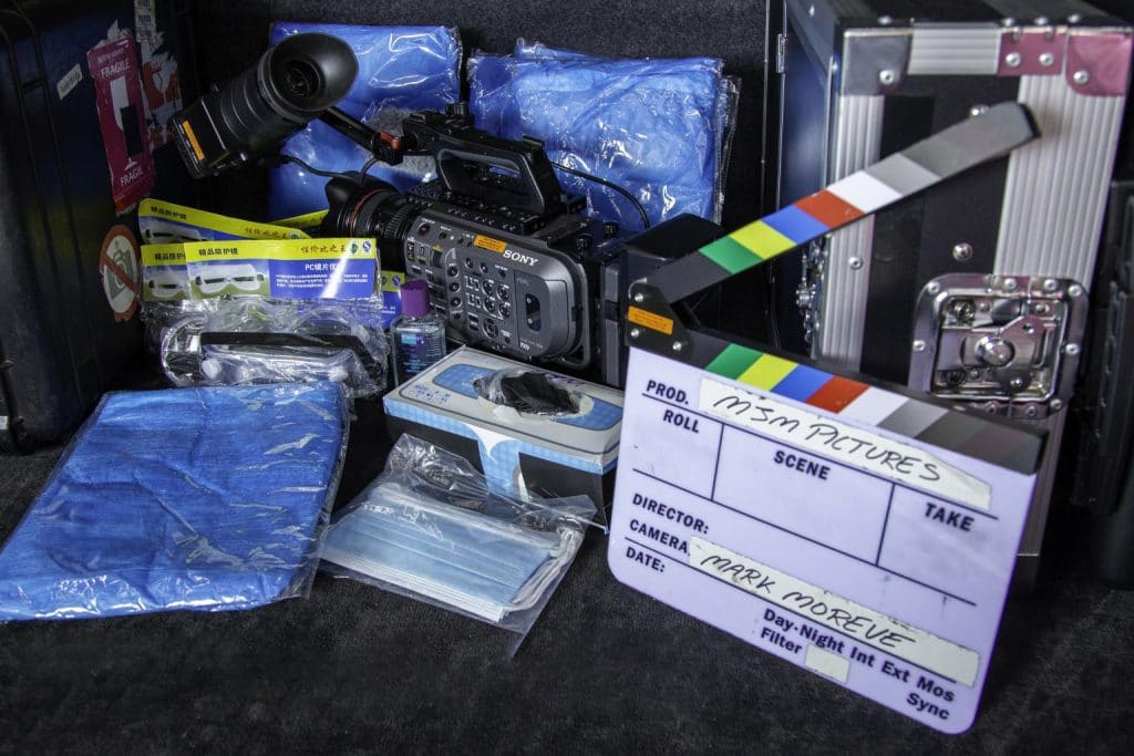 ppe in the back of a van with a clapperboard in the foreground