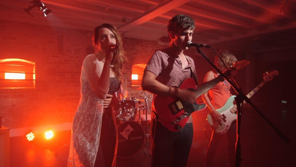 two performers in a basement lit by red light