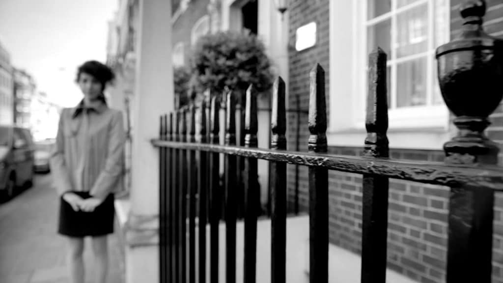 A shot of some railings with a person out of focus in the background, the image is black and white
