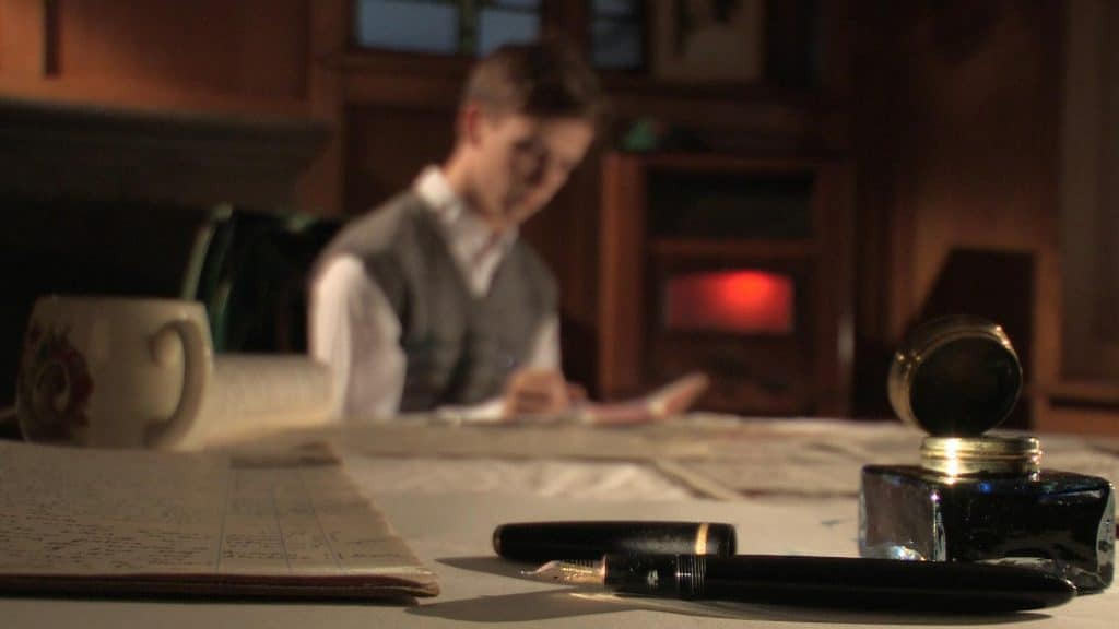 a close up of an old writing desk with a fountain pen and ink well