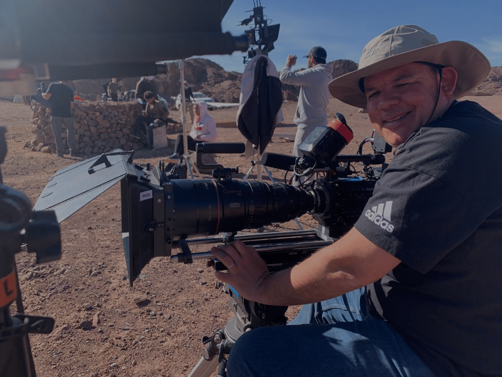 mark sitting behind a camera in the desert. the camera has a large lens and mattebox on the front