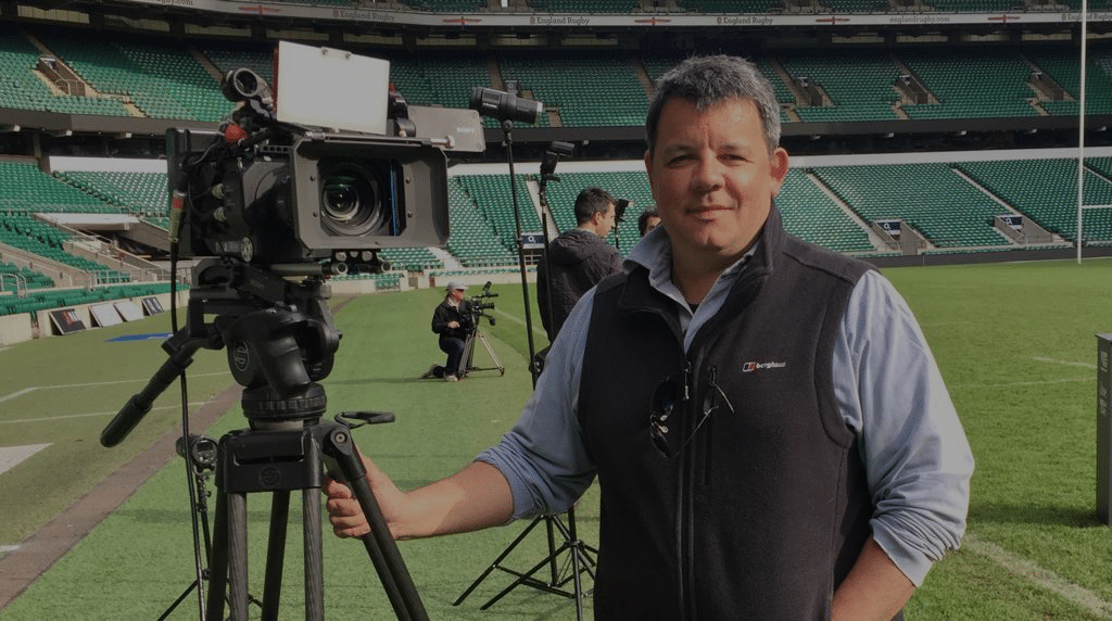 mark standing next to a camera in a rugby ground