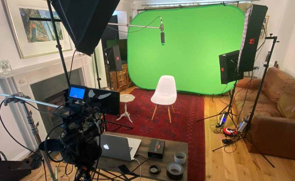 a greenscreen setup with a chair, lighting and a boom mic. there is a camera in the foreground